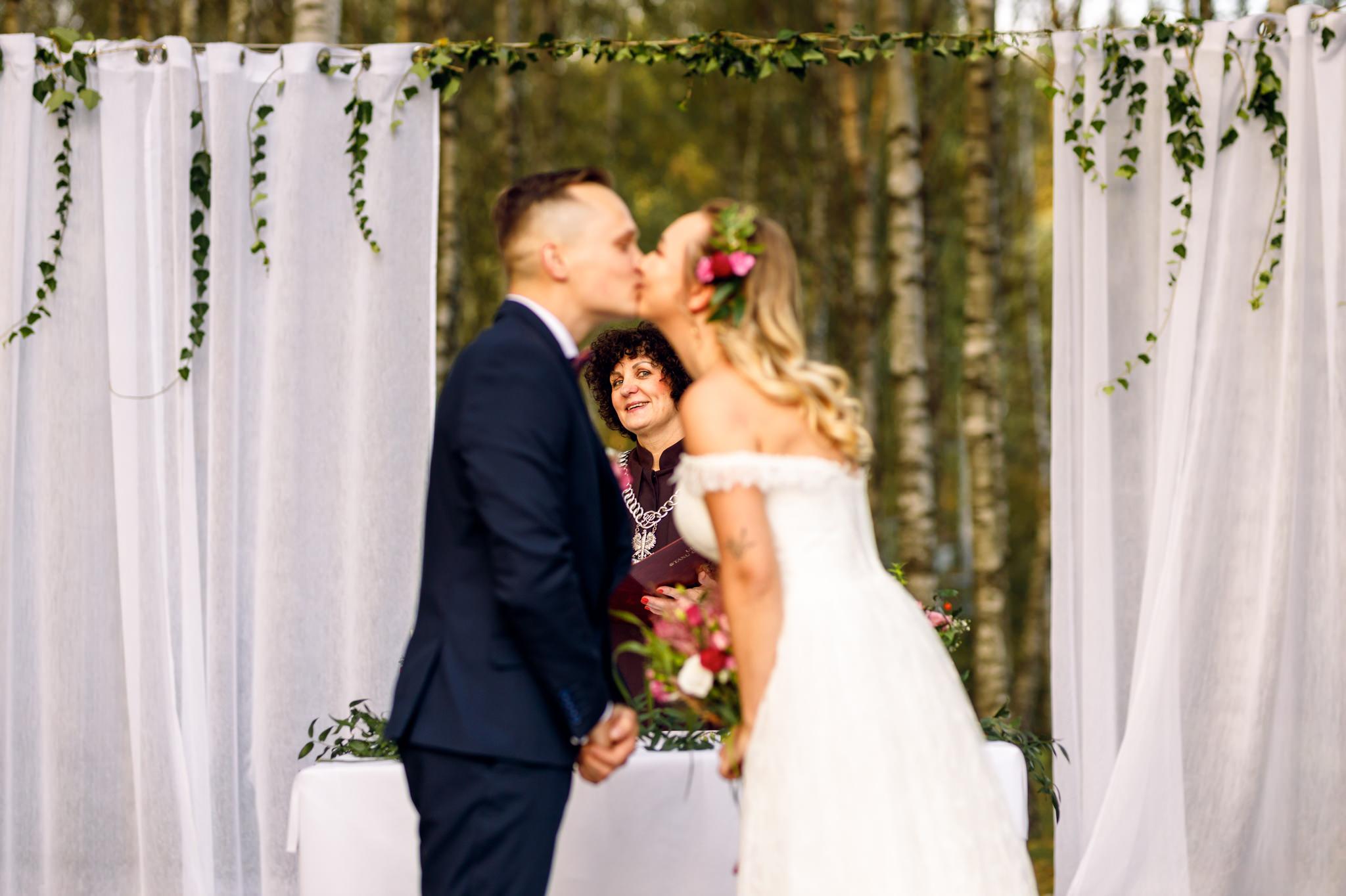 pocałunek pary młodej podczas ślubu plenerowego