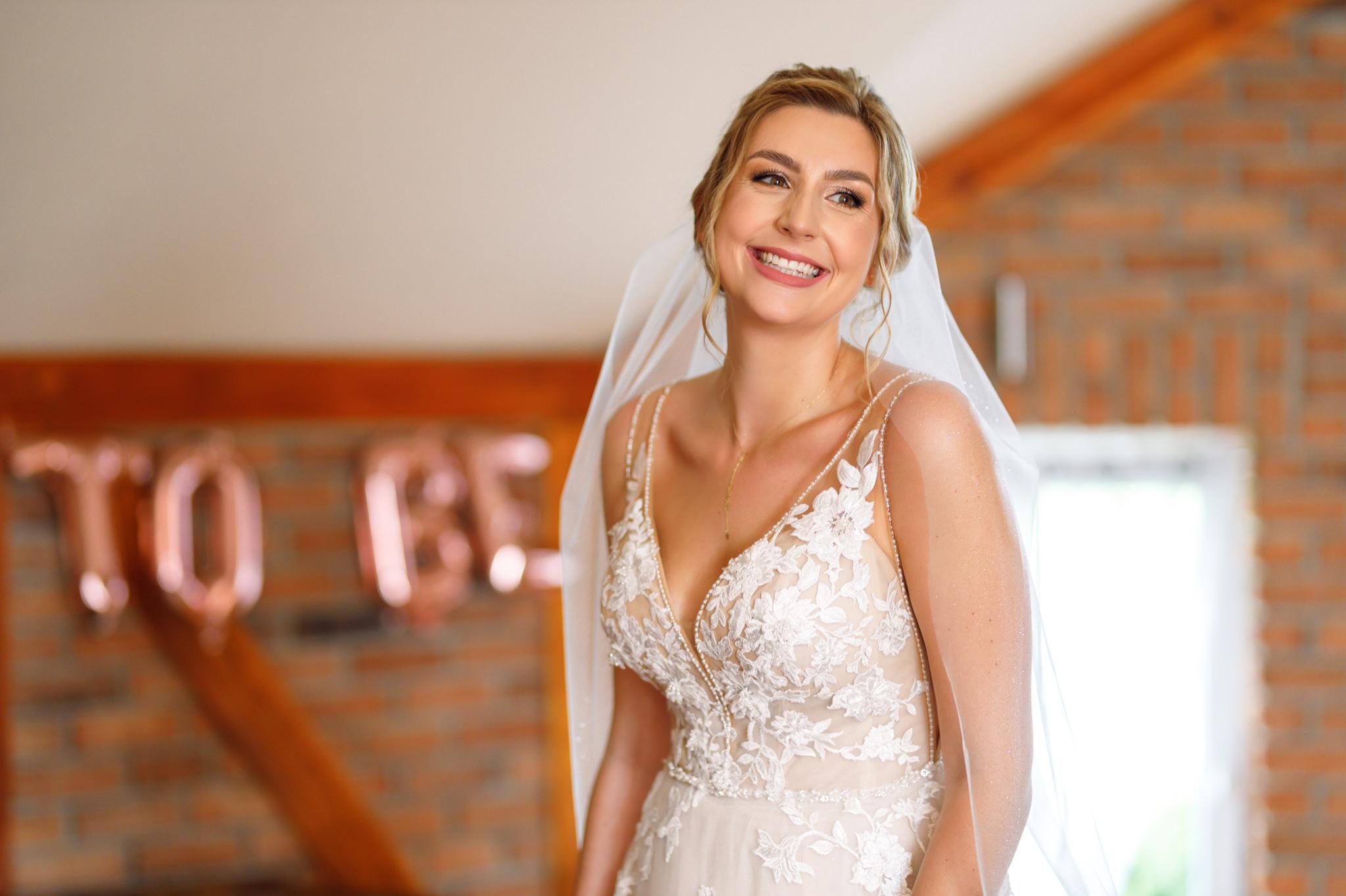 uśmiechnięta panna młoda podczas przygotowań do ślubu