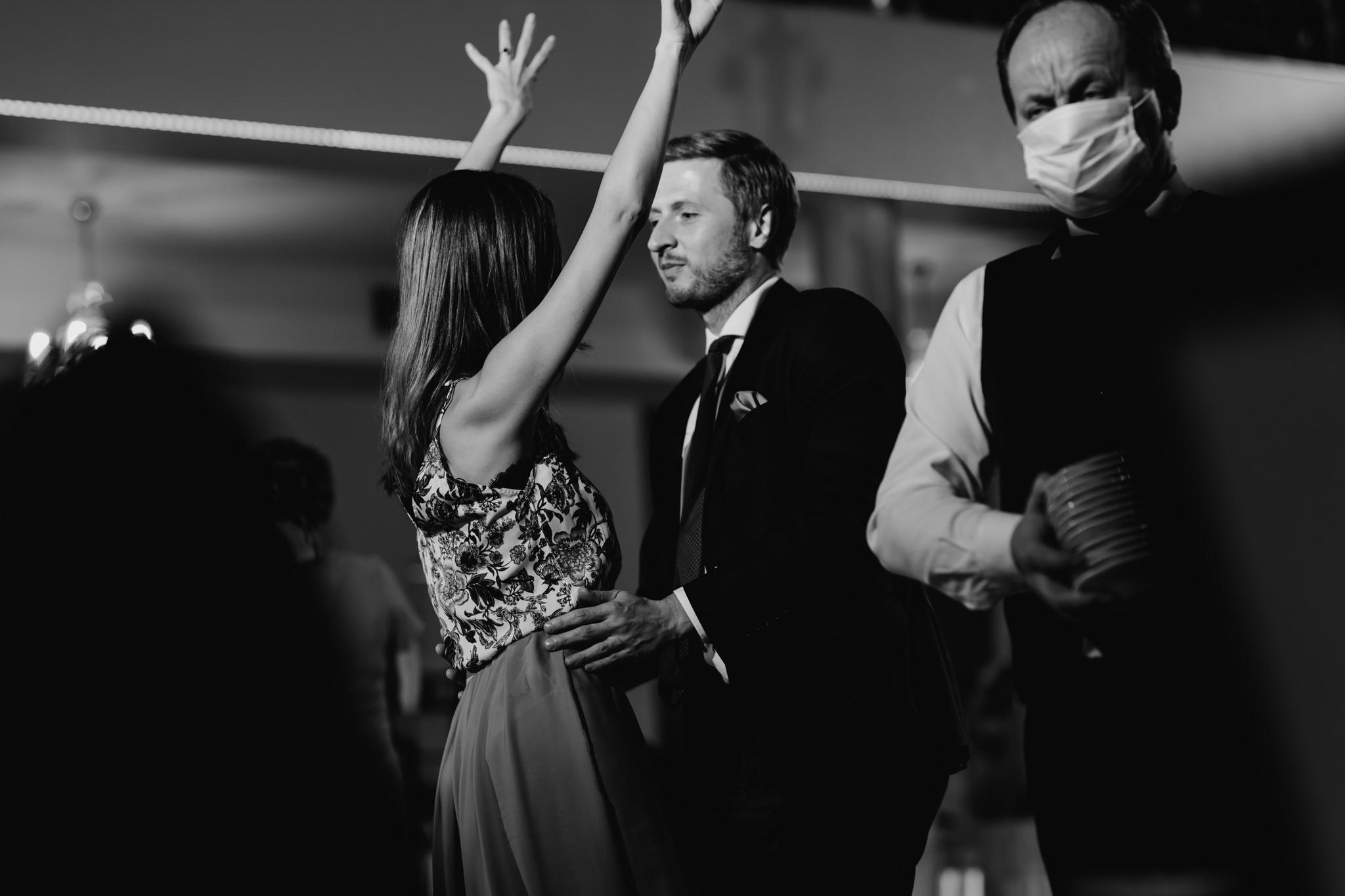 tańcząca para obok kelnera w maseczce