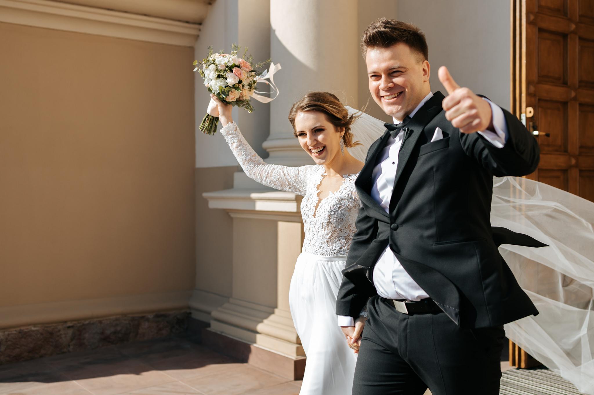 radosna para młoda wychodzi z kościoła Fotograf ślubny Warszawa